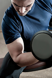 Young man in gym lifting dumbbell