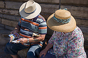 Elderly visitors to Weston-super-Mare read an events brochure on the seaside resort's seafront. We look down on the tops of their heads and straw hats, both circular with bands - one for women and another for men. The husband has a walking stick and tattoo on his forearm and wears stripes while the woman is in floral patterns - both gender fashion stereotypes.