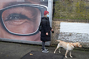 With one eye from half of a Specsavers billboard ad, a dog owner stands with a labrador on the platform of Denmark Hill Station in south London, on 6th November 2020, in London, England.