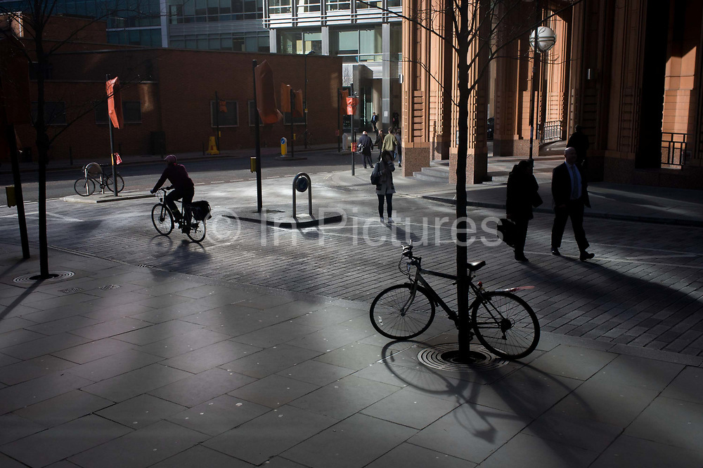 A theme of locked and pedalled bikes on reflected lit street corner in the City of London. In a bright area of reflected sunlight, we see a wide section of a road junction near the 1980s Broadgate development where pedestrians and cyclists share the urban landscape. A bike is locked up against a tree; another at a distant pole while a third is being ridden towards the T-junction.