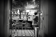 A man lights a cigarette in the doorway of a New Orleans restaurant