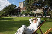 Woman sunbathing in gardens of the Priory Hotel, Wareham, Dorset, England, UK