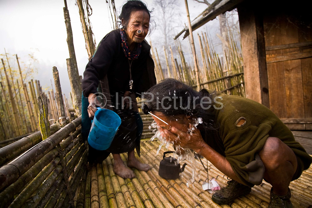 """Apatani tribal elders Atta Yadd and her husband Ba Khang wake up in the early morning, freshen up on the raised bamboo platform of  their one roomed """"open plan"""" bamboo made stilted hut, sleeping on mats in the center close to the bamboo fire which is protected by a brick-lined hearth in the village of Hijja, Arunachal Pradesh. The Apatani tribe are one of hundreds of indigenous tribes scattered across India, particularly the north east. Their origins are from Mongolian nomadic tribes whom settled on the Ziro plateau, close to the Chinese border, they practice fixed agriculture as well as forestry, planting trees on the rim of the plateau as well as bamboo forests from which they derive fire wood, building their homes as well as using the bamboo for all manner of applications in their daily lives, cooking utensils and household containers amongst other uses. They carefully cultivate bamboo forests allowing them to grow, but not flower and die, as this would spell disaster for their very own existence. They also tend to their rice fields and live stock for what is mostly a subsistence economy. The Indian constitution recognizes over 500 indigenous tribes, which account for 8.5% of the total population"""