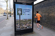 Runner passes a sign ad the planned expansion of the Ultra Low Emission Zone, also known as ULEZ on 5th March 2021 in London, United Kingdom. Transport for London are using this pollution reduction initiative to improve air quality, by charging more polluting vehicles such as diesel and older vehicles to enter the ULEZ zone, which currently is the same area as the congestion zone.