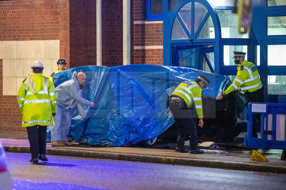 © Licensed to London News Pictures. 11/11/2020. London, UK. Police officers and a forensic investigator cover a vehicle at the entrance of Edmonton Police station. A vehicle has crashed into Edmonton police station, the incident occurred at approximately 18:58GMT. Photo credit: Peter Manning/LNP