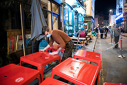 "© Licensed to London News Pictures; 25/09/2020; Bristol, UK. The city centre is much quieter than usual as staff clean and stack tables to close licensed premises on the first weekend of the 10pm early closing curfew for pubs, bars and restaurants across the UK, imposed by the government to try and halt a second wave of the covid-19 coronavirus pandemic. Gathering in groups of more than six people is also banned and there are penalties of £200 on the first offence. From Monday 14 September it was illegal to meet up socially in groups of more than six people, known as the ""Rule of Six"", in order to try and contain the spread of the covid-19 coronavirus pandemic. Photo credit: Simon Chapman/LNP."