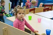 Nederland, Veghel, 20101117.?Meisje op de creche. Ze kijkt in de camera. Aan tafel met gekleurde drinkbekers.?Kinderopvang 't Kroontje in Veghel...Netherlands, Veghel, 20101117. ?Girl on the nursery. She looks into the camera. At the table with colored goblets.?Childcare t Kroontje in Veghel..