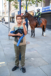 © Licensed to London News Pictures . 09/08/2011 . Manchester , UK . A boy standing on Market Street , sticks his middle finger up , as disorder spreads to Manchester during a 4th night of rioting and looting , following a protest against the police shooting of Mark Duggan in Tottenham . Photo credit : Joel Goodman/LNP