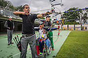 """2016/04/28 – Medellín, Colombia: German Gomez, 49, practices arrowing with a few colleagues at the Belen Sports Complex, Medellin, 28th April, 2016.<br /> -<br /> German used to look for gold with his father on the region of Choco. But the National Liberation Army (ELN) started to threaten them and wanted Germans family to pay to the ELN for """"protection"""". Because German's family refused to pay, they had to leave their village and everything behind. They became displaced. Despite this, the guerrilla did not stop chasing them and when they found them, German and his father were both shot. His father died. German suffered an injury in his last vertebra, becoming paraplegic. <br /> With the help of a Foundation that supports victims through sports, German started his rehabilitation program. First, he started with swimming, he had never swum before but only after 6 months he won a silver medal at a competition. But months later he had a cramp while practising, and almost drown. The incident made him so afraid that he's never returned to a swimming pool again. <br /> As German was good at shooting in the army, he decided to try a sport that requires this skill. He started to focus on arrowing and after a few months he qualified for the 2015 Pan-American Games where he finished in 5th place. German managed to qualify to the Rio 2016 Paralympic, and his goal is not only to get a good result, but he also needs it in order to get a sponsorship that will allow him to live off his sport. Currently, he fixes broken computers and smartphones between practices and competitions to pay his bills. (Eduardo Leal)"""
