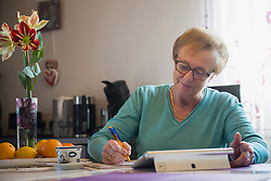 Old woman watching digital tablet and writing in book at dining table
