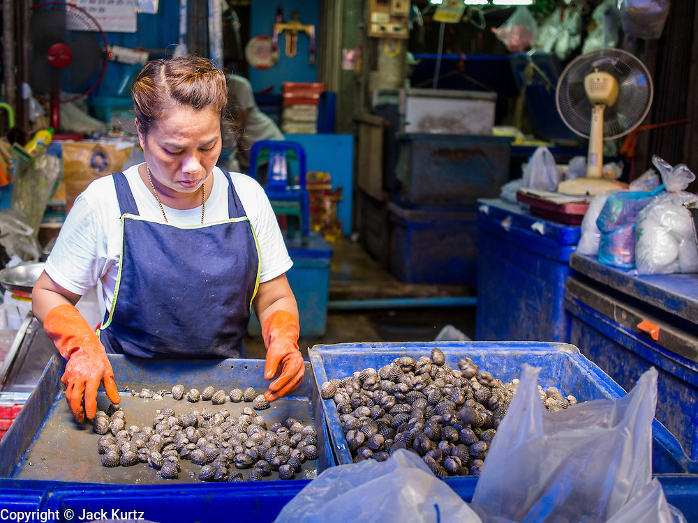 """03 APRIL 2014 - BANGKOK, THAILAND:   A vendor sorts cockles in Khlong Toey Market in Bangkok. Khlong Toey (also called Khlong Toei) Market is one of the largest """"wet markets"""" in Thailand. The market is located in the midst of one of Bangkok's largest slum areas and close to the city's original deep water port. Thousands of people live in the neighboring slum area. Thousands more shop in the sprawling market for fresh fruits and vegetables as well meat, fish and poultry.     PHOTO BY JACK KURTZ"""