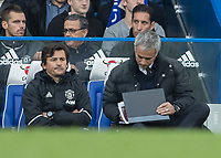 Football - 2016/2017 Premier League - Chelsea V Manchester United<br /> <br /> Manchester United Manager Jose Mourinho writes notes in his book during the game at Stamford Bridge.<br /> <br /> COLORSPORT/DANIEL BEARHAM