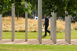 Hyde Park, London, July 7th 2015. As Londoners remember the tenth anniversary of the 7/7 bombings, a man walks through the memorial in Hyde Park to lay a boquet of flowers.