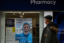 © Licensed to London News Pictures. 26/10/2021. London, UK. A man looks at 'Free NHS Flu Jab' poster displayed in Boots pharmacy in Wood Green, north London. People are being urged to get their flu jab ahead of the winter as figures from the drug maker Reckitt suggest that the cold and flu season will be worse this year than normal. Health Secretary Sajid Javid is considering making flu jabs mandatory for all NHS staff.   Photo credit: Dinendra Haria/LNP