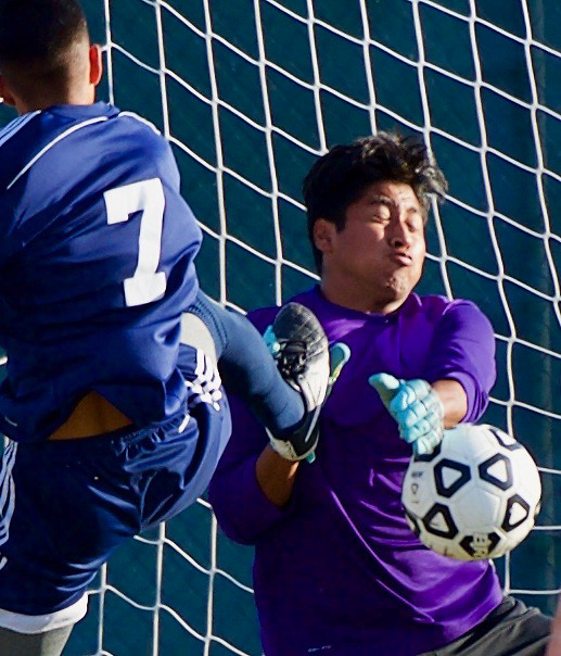 Golden West goal keeper takes on Fullerton forward Steven Garcia (7) in second half play of Golden West's 1-0 win.
