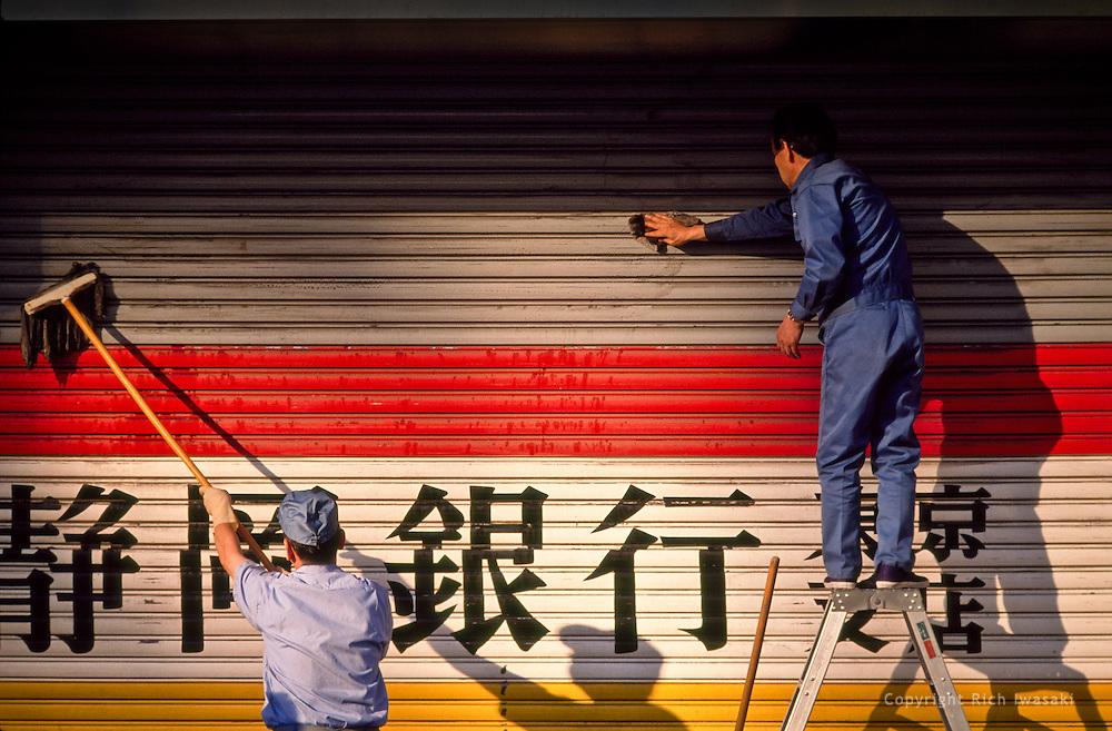 Workers clean security door of Shizuoka Bank, Tokyo branch, Marunouchi district, Tokyo, Japan