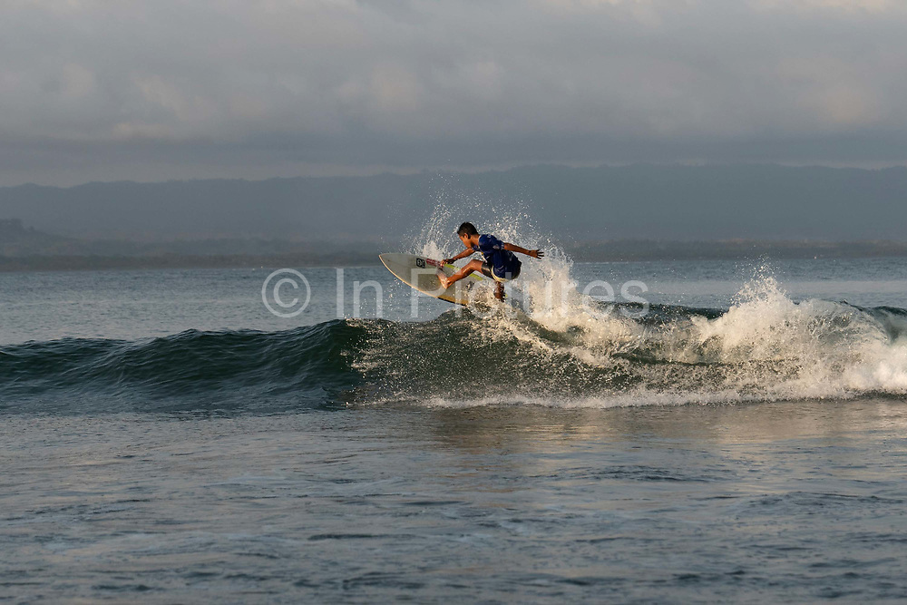 A male Indonesian surfer at Batu Karas beach on the 31st October 2019 in Java in Indonesia.