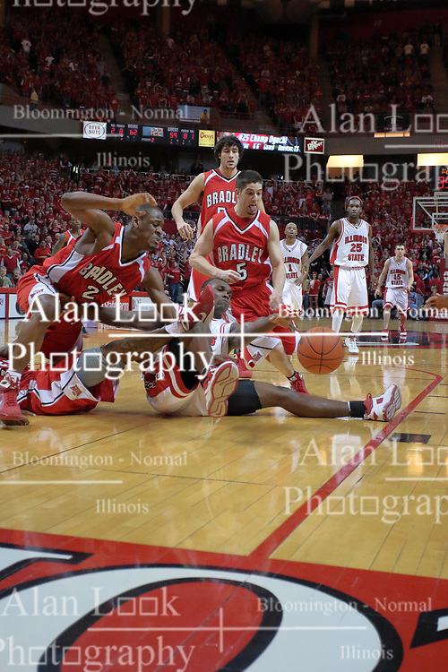 "31 January 2009: Dinma Odiakosa reaches out for the ball while on the floor but can't reach it.  Eddren McCain and Sam Maniscalco out flank Odiakosa, staying on their feet. The Illinois State University Redbirds join the Bradley Braves in a tie for 2nd place in ""The Valley"" with a 69-65 win on Doug Collins Court inside Redbird Arena on the campus of Illinois State University in Normal Illinois"