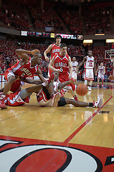 """31 January 2009: Dinma Odiakosa reaches out for the ball while on the floor but can't reach it.  Eddren McCain and Sam Maniscalco out flank Odiakosa, staying on their feet. The Illinois State University Redbirds join the Bradley Braves in a tie for 2nd place in """"The Valley"""" with a 69-65 win on Doug Collins Court inside Redbird Arena on the campus of Illinois State University in Normal Illinois"""