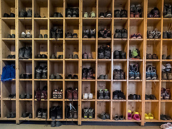 Shoe rack full with hiking boots inside mountain hut near Cauterets in High Pyrenees, France