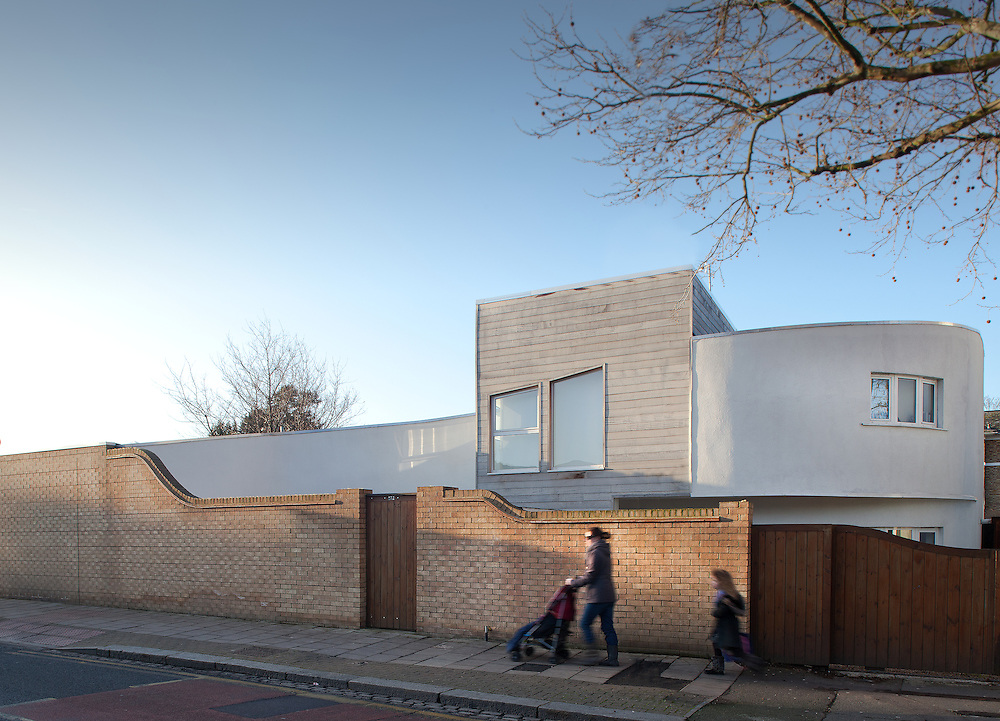 Modern house with wood cladding and white render in denmark hill in London.