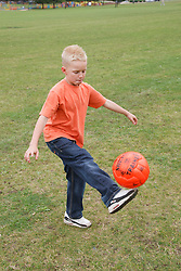 Boy playing with football.