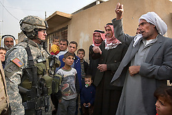 Maj. Jonathan Fox, talks to Iraqis while on patrol with other members of the 1st Infantry, 17th Regiment, Mosul, Iraq, Dec. 16, 2005. This is part of an effort to provide security in preparation for Iraq's first post-Saddam parliamentary elections. The western sector is home to Mosul's primarily Sunni population, which has been resistant to the American presence in Iraq.
