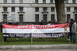 London, UK. 3rd July, 2021. Anti-coup activists hold a banner during a protest opposite Downing Street against political executions in Egypt on the 8th anniversary of the Egyptian military coup against President Mohamed Morsi. 92 political prisoners have been executed in Egypt since the coup, with death sentences ratified by General Abdel Fattah el-Sisi for a further 64.