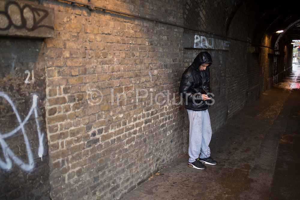 Young Asian man shelters sending texts under a railway bridge to stand under cover from the rain on a wet rainy day in Whitechapel, East End of London, UK.