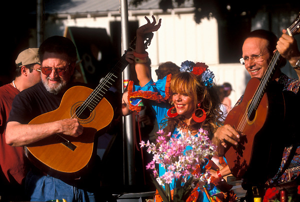 Stock photo of a woman with two guitar playing men at the International Festival in downtown Houston Texas