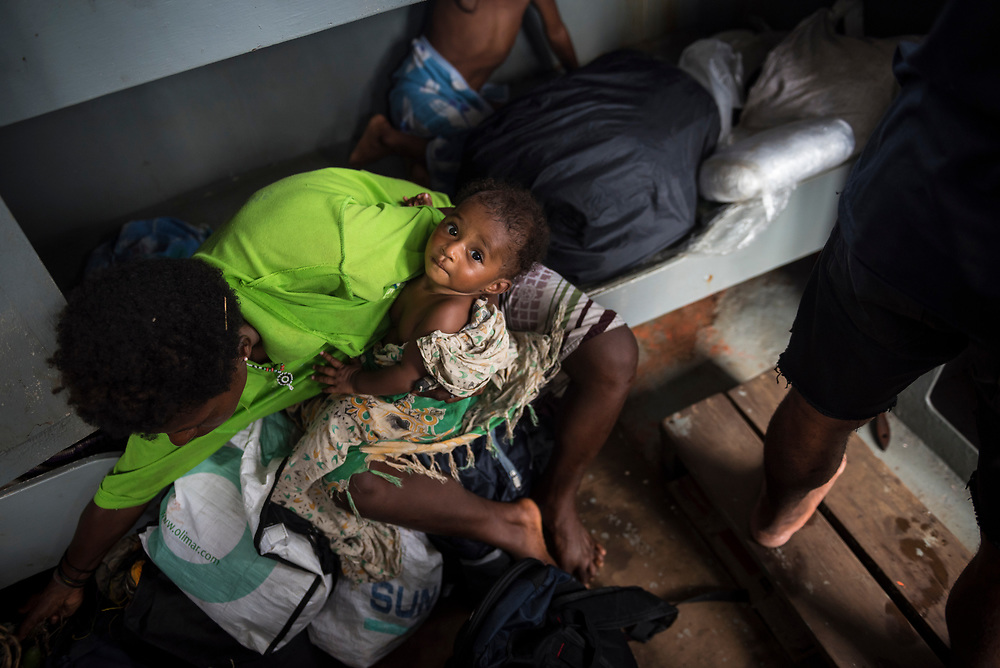 A mother holds her baby on a boat that transports copra (dried coconut), passengers, and other cargo from Karkar Island to the mainland port of Madang, Papua New Guinea. (August 2017)