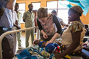 Dr Siobhan Neville examines a patient on the children's ward during the daily rounds.  The rounds are attended by all the medical staff who work on that ward, doctors, nurses and attendants.  St Walburg's Hospital, Nyangao. Lindi Region, Tanzania.