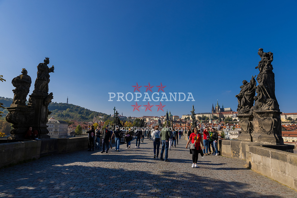 PRAGUE, CZECH REPUBLIC - Friday, October 8, 2021: Tourists on the Charles Bridge (Karlův most) with Prague castle in the background. (Pic by David Rawcliffe/Propaganda)