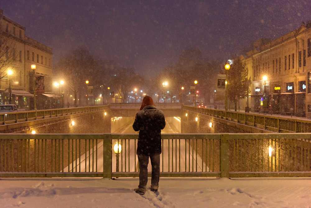 """A man snaps a photo of largely deserted Connecticut Ave around Dupont Circe during the beginning of the """"snowzilla"""" blizzard on Friday evening, January 22, 2016 in Washington, D.C."""