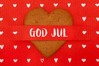 Julehilsen-tekst «God jul» på sammen med pepperkakehjerter og hvite hjerter på grovfibret rødt papir.