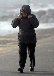 © Licensed to London News Pictures. 24/10/2011. Felixstowe, UK. A woman hold onto her hood to prevent the wind blowing it down. Windy weather along Felixstowe promenade today 24th October 2011. Parts of the UK are braced for wet and windy weather over the next 24hrs . Photo: Stephen Simpson/LNP