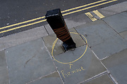 A detail of a section of pavement where a post has been damaged and is being marked for removal by a circle drawn around its base, on 6th November 2020, in London, England.