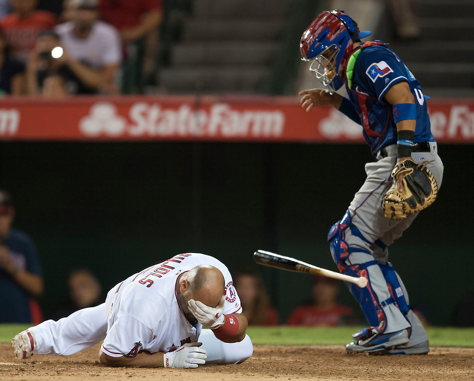 The Angels' Albert Pujols falls to the ground after being hit in the head by a pitch in the seventh inning in front of Rangers' catcher Robinson Chirinos at Angel Stadium on Tuesday.<br /> <br /> ///ADDITIONAL INFO:   <br /> <br /> angels.0720.kjs  ---  Photo by KEVIN SULLIVAN / Orange County Register  -- 7/19/16<br /> <br /> The Los Angeles Angels take on the Texas Rangers at Angel Stadium.