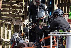 Denham, UK. 22nd March, 2021. Bailiffs from the National Eviction Team (NET) use cherry pickers during a large security operation with Thames Valley Police to remove activists opposed to the HS2 high-speed rail link from a makeshift tower where they were seeking to delay electricity pylon relocation works by Babcock in Denham Country Park.