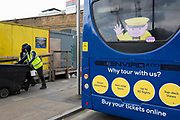 The recognisable face of the sightseeing company Megasightseeing, on the rear of a parked bus and a warning sign of bike theft, on the Southbank, on 2nd May 2019, in London, England. Megasightseeing is part of the Megabus, a long distance coach operator operated by the Stagecoach Group. It commenced operating in August 2003, initially in the United Kingdom, and later expanding into continental Europe.