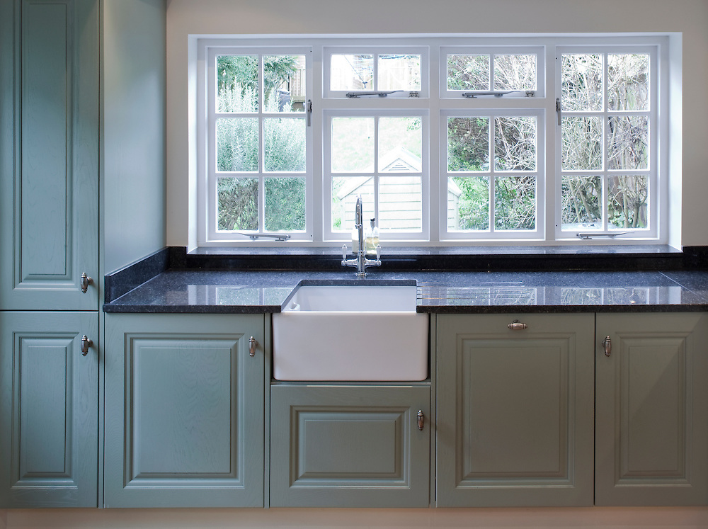 Green kitchen units with belfast sink and windows looking out onto garden