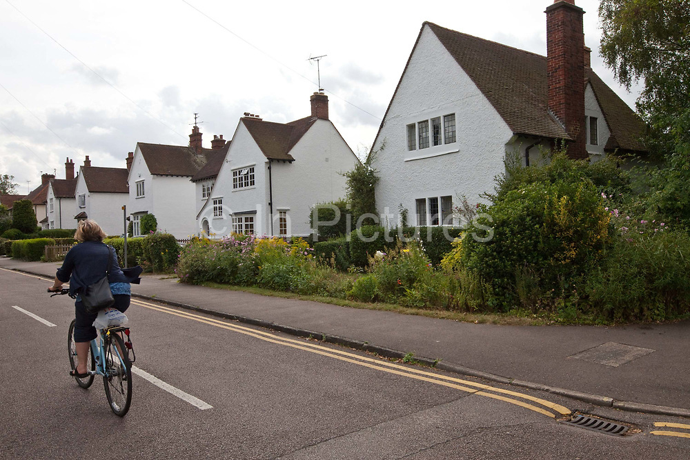 """A woman cycles her bicycle past Arts and Crafts period houses in Letchworth, the world's first Garden City designed by Ebenezer Howard to marry the best of urban and rural living.<br /> In 1898 Ebenezer Howard published his book """"Tomorrow: A Peaceful Path to Reform"""" (later """"Garden Cities of Tomorrow"""") founding the Garden Cities Association. His plan was to create a new, planned  settlement that combined the best of town and country - the first of which became Letchworth Garden City in 1903, laid out by architects Barry Parker and Raymond Unwin. It was followed in 1920 by a second garden city at Welwyn. The movement inspired Garden Cities in Europe and currently has been revived as a potential solution to Britain's housing crisis"""