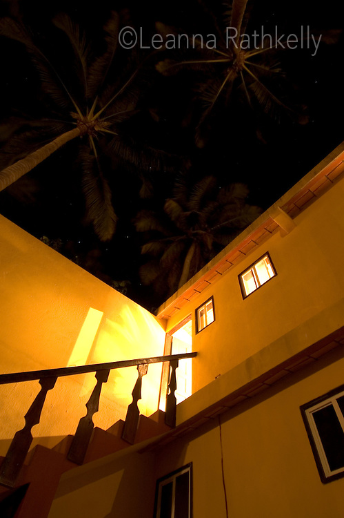 A stairway on the adobe buildings of the Sayulita Trailer Park rise up to palm trees at night.