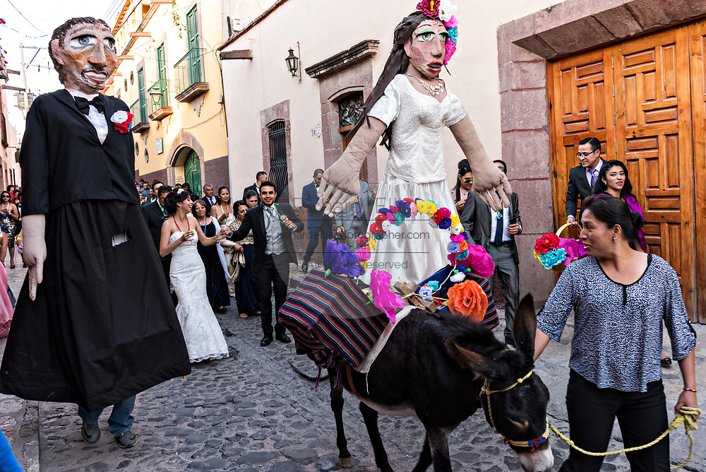 A decorated donkey leads the way as giant puppets called mojigangas dance during a wedding celebration parading through the streets San Miguel de Allende, Guanajuato, Mexico.