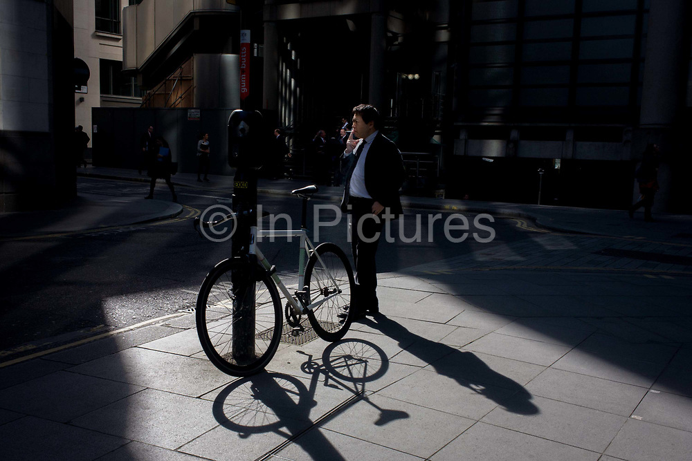 Businessman and locked up bicycle in sunlight corner of a precinct outside a large City of London financial institution in Lime Street. The man inhales from his cigarette in a quiet moment between work commitments and long shadows from afternoon light that finds its way between tall office buildings throws its shadows on the pavements and walls of modern architecture. Bikes can be locked on posts as people stroll between meetings at nearby the nearby Lloyds insurance market.