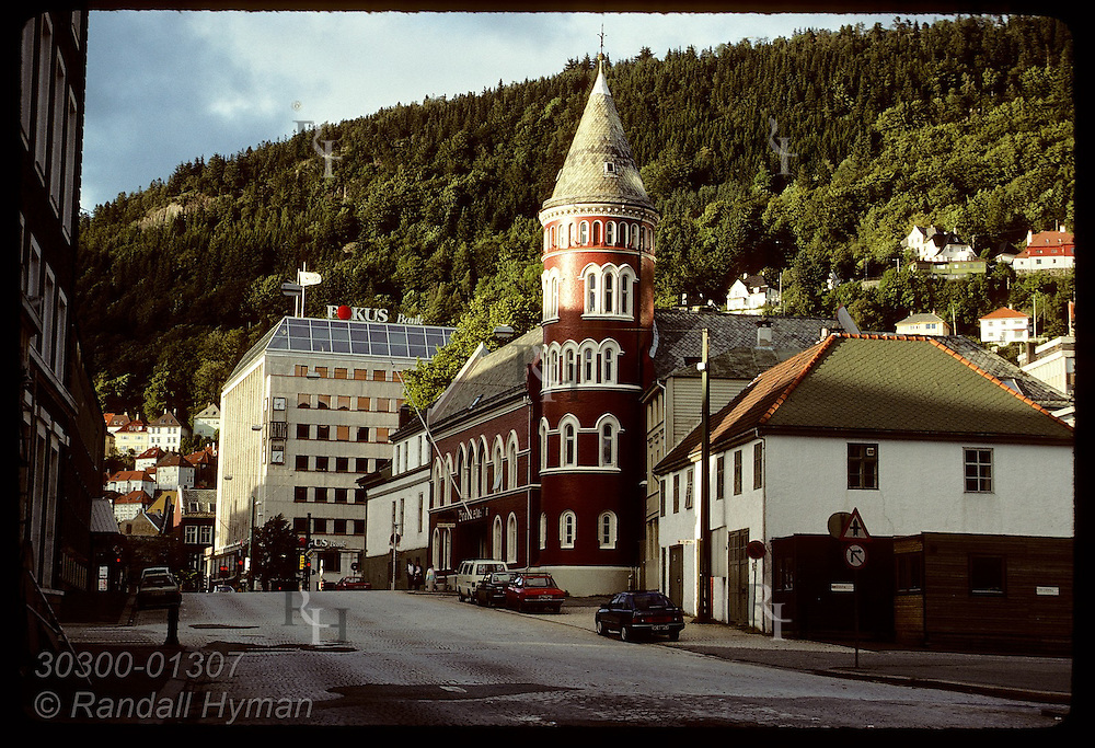 Ornate turret of red brick building catches late sun of a summer eve on downtown street in Bergen Norway