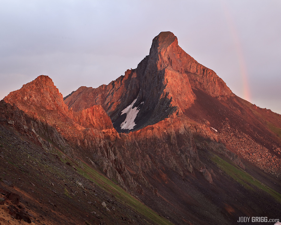 A break in the storm at sunset brings a rainbow over Wetterhorn Peak in the San Juan mountains.