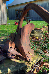 07 October 2013:  Two 1800 era barns stand on the property of the Heritage House near Nashville Indiana in Brown County.  A rusty steel plow now does duty as a yard decoration<br /> <br /> This image was produced in part utilizing High Dynamic Range (HDR) processes.  It should not be used editorially without being listed as an illustration or with a disclaimer.  It may or may not be an accurate representation of the scene as originally photographed and the finished image is the creation of the photographer.