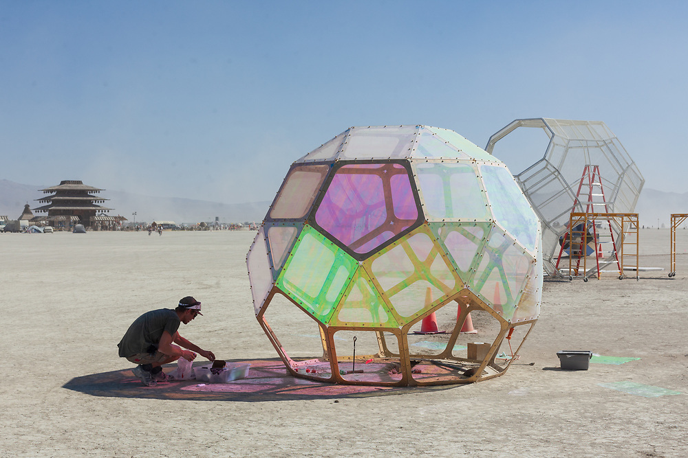 HYBYCOZO - Heart of Gold from: San Francisco, CA year: 2016<br /> <br /> Sculpture 1- The Improbability Drive will consist of an all-pipe skeletal frame connecting into a mirrored hypercube shape made of mirror. The inside shape, a rhombic dodecahedron, has an optical illusion that looks like 3 different shapes in 3 different perspectives. The mirror shape on the inside will reflect the outside edges, creating a 4D dimensional hypercube effect. Sculpture 2- The Heart of Gold – will consist of a skeletal frame of a rhombic triactohedron and from its top-most point will hang a super intricate laser cut HYBYCOZO sculpture that will cast shadows far into the playa. This outer skeletal shape is the most complex shape that DaVinci drew and will form a super fun dome-like jungle gym. Sculpture 3- Hyperspace Bypass- A stacked set of 11 HYBYCOZO rhombic dodecahedrons shapes set on top of each other tessellating perfectly in 3D space. Its form is reminiscent of an iceberg or a 4D pyramid. In the day it will looking like a gleaming gold multifactored pyramid. URL: http://www.hybycozo.com Contact: hybycozo@gmail.com