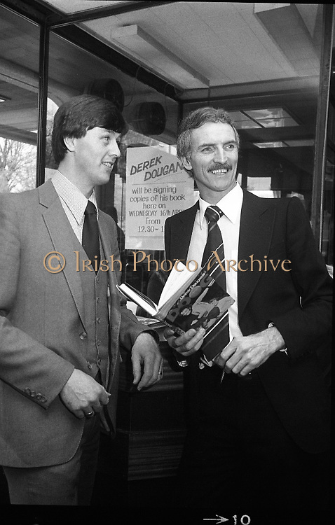 Derek Dougan's name goes in the book...1980-04-16.16th April 1980.16-04-1980.04-16-80..Photographed at Hodges Figgis, Stephen's Court, St Stephen's Green, Dublin:..Fromer Northern Irish soccer international and English League player Derek Dougan signing a copy of his book 'Doog' for a customer.